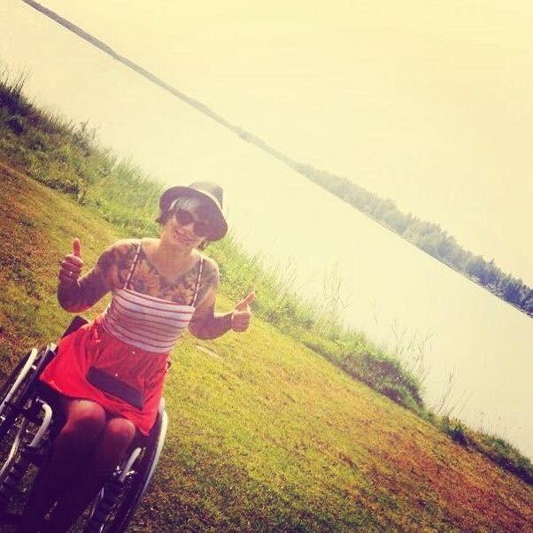 Uśmiechnięta Izabela Sopalska-Rybak na tle jeziora z rękami delikatnie uniesionymi pokazująca kciuki do góry