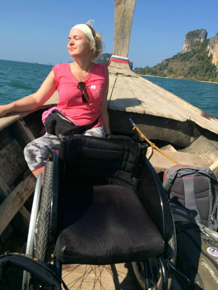 Angelika Chrapkiewicz-Gądek w Tajlandii na drewnianej łodzi. Wygrzewa się w słońcu a przed nią stoi wózek
