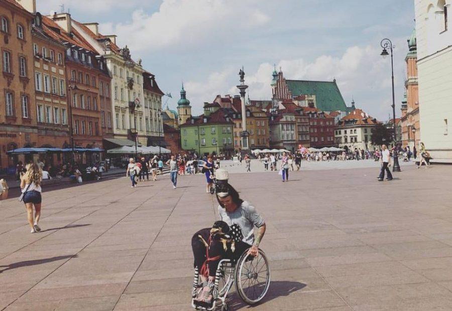 Izabela Sopalska-Rybak, poruszająca się na wózku z psem na kolanach, na starówce.