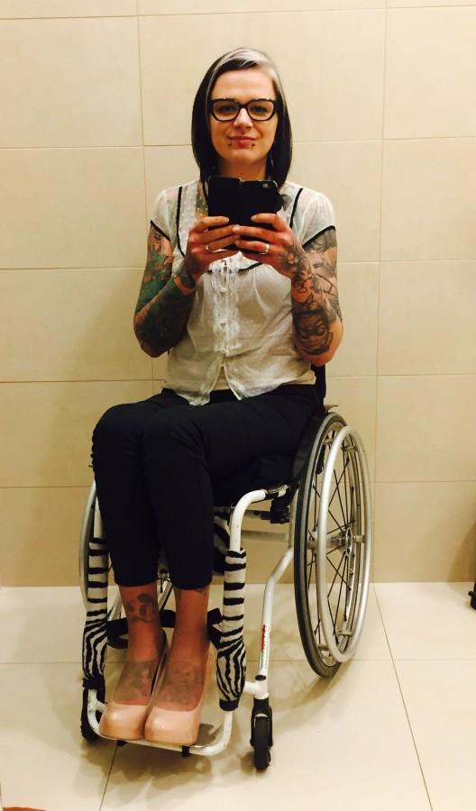 Izabela Sopalska-Rybak, prezeska Fundacji Kulawa Warszawa w eleganckim stroju, na wózku robi sobie zdjęcie w lustrze.