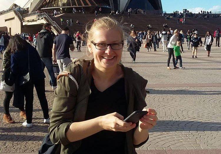 Uśmiechnięta kobieta o blond włosach, w średnim wieku, w okularach, ciemnozielonej kurtce trzyma w dłoniach telefon komórkowy. W tle tłum ludzi i Sydney Opera House.