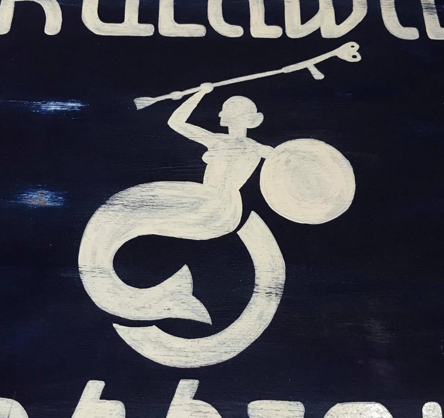białe logo Fundacji Kulawa Warszawa namalowane na granatowym tle